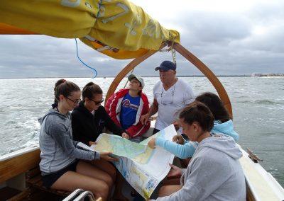 Jeunes filles lisant une carte sur une pinasse